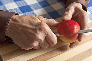 Hands cutting an apple with a knife